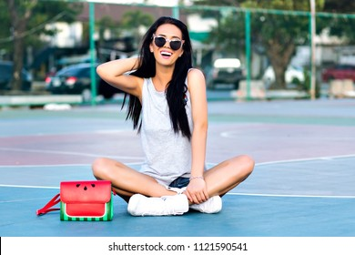 Excited brunette woman sitting with legs crossed at basketball court and playing with her hair. Outdoor portrait of smiling girl in sunglasses posing on the ground near bag with watermelon design.
