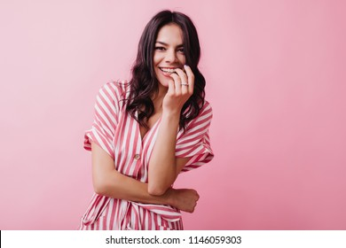 Excited brunette woman wears ring smiling on pink background. Indoor photo of gorgeous dark-haired girl in elegant striped dress.