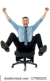Excited business man with arms raised while sitting