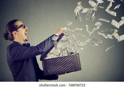 Excited business man opening an box letting dollar banknotes to fly away