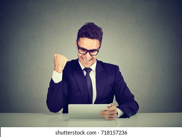Excited business man reading good news on line on a tablet computer sitting at table in his office