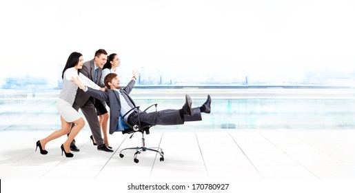 excited business people group team push colleague leader sitting in chair, young businesspeople smile raised hands arms, concept of human resources