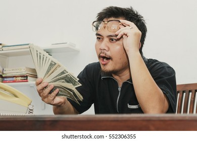 Excited businessman is holding the money in hand. Working illegally