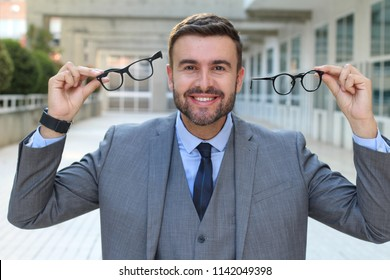 Excited businessman holding two pair of eyeglasses
