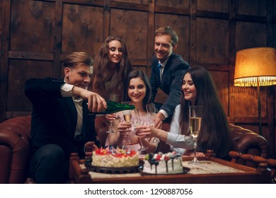 Excited businessman pours champagne at his bithday party. Young man in dark suit pours the champagne to his close friends