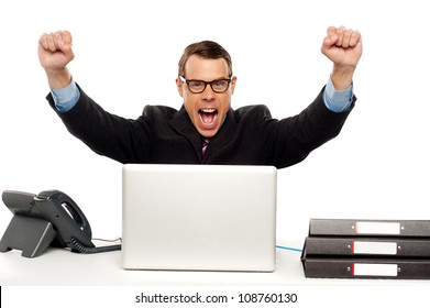 Excited businessman shouting and rejoicing his victory. Wearing glasses and arms raised up