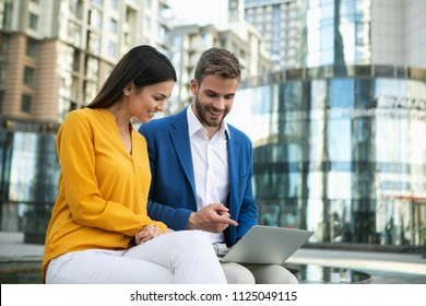 Excited businessman showing presentation on laptop to his colleague. Woman is looking at gadget with interest and smiling with satisfaction. They are sitting outdoor in city