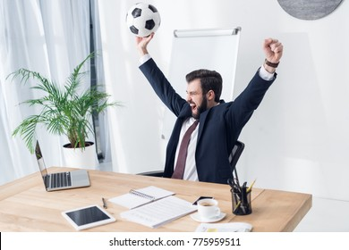 excited businessman in suit with soccer ball at workplace in office