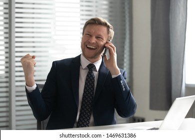 Excited businessman in suit triumph having pleasant important conversation on cellphone make successful business deal, overjoyed male CEO feel euphoric succeed talking on smartphone with client