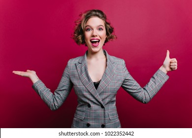 Excited business-woman in elegant gray attire having fun during photoshoot. Studio shot of enthusiastic girl in formal style jacket waving hands on claret background.
