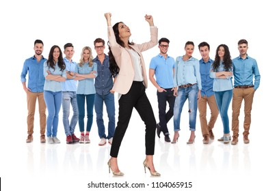 excited businesswoman group leader celebrating with both hands in the air and looking up to side while standing in front of her team on white background