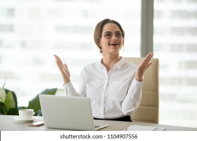 Excited businesswoman raising hands amazed or happy with great news, grateful for business success, online win, impressive achievement, found surprising easy corporate solution or got new good idea