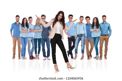 excited businesswoman team leader presenting her casual group standing behind her on white background with both hands pointing up and leaning to side
