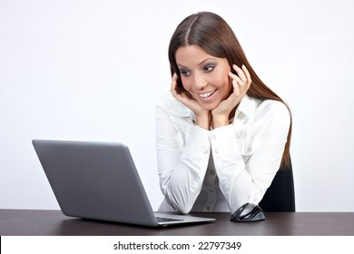 Excited businesswoman using laptop in office.