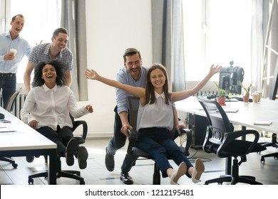 Excited carefree diverse young office workers having fun during work break, multi-ethnic colleagues riding on chairs enjoying funny game, employees coworkers feeling free laughing playing together