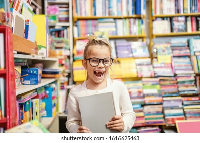 Excited caucasian cute little blond girl with eyeglasses and ponytail standing in bookstore and holding book she was looking for.