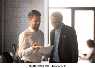 Excited Caucasian employee show company financial statistics to boss or colleague, praising high results or achievement, proud male worker present paperwork stats to team leader, happy with success