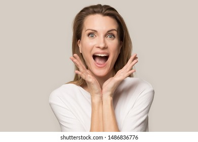 Excited Caucasian millennial woman in casual clothes isolated on grey studio background scream with happiness, smiling happy female shout yell fell euphoric and overjoyed about great sales, discounts