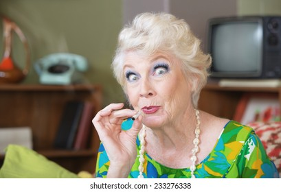 Excited Caucasian senior woman in green smoking marijuana