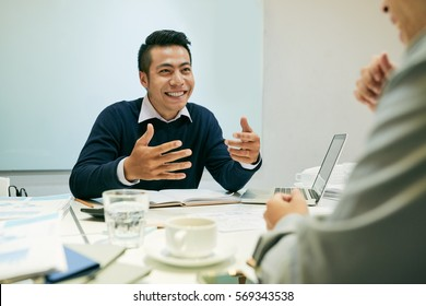 Excited cheerful businessman explaining something to coworker