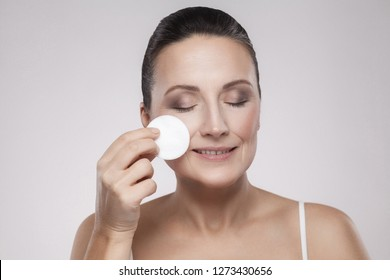 Excited cheerful confident lovely beautiful mature woman is using a cotton pad with micellar water for removing make up from face, isolated on grey background, copy space, studio shot, indoor