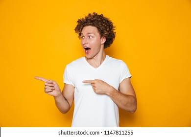 Excited cheerful man 20s with brown curly hair gesturing finger aside on copyspace isolated over yellow background