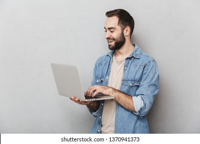 Excited cheerful man wearing shirt isolated over gray background, showing laptop computer