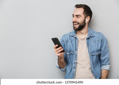 Excited cheerful man wearing shirt isolated over gray background, wearing earphones, using mobile phone