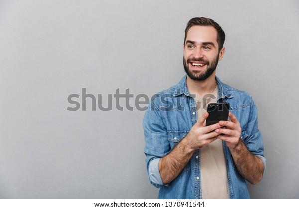 Hombre alegre y emocionado con pantalones aislado sobre fondo gris, usando teléfono móvil