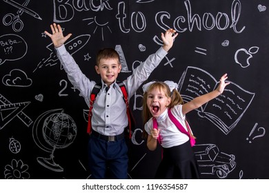 Excited and cheerful schoolkids standing before the chalkboard as a background with a backpack on his back showing happy emosions by means of raised hands.