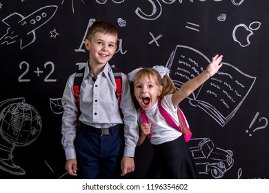 Excited and cheerful schoolkids standing before the chalkboard as a background with a backpack on his back showing happy emosions. Landscape picture.