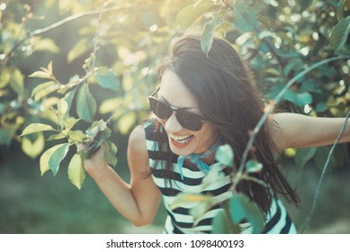 Excited, cheerful young woman enjoying a wonderful day in nature, jumping around, running and feeling extremely happy