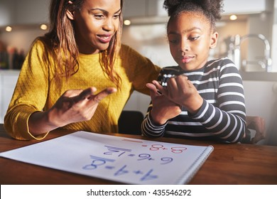 Excited child learning to calculate at home, black mother and daughter doing homework