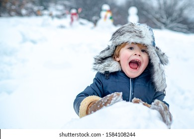 Excited Child playing with snow in park on white snow background. Winter children in frosty winter Park. Cute kid - winter portrait. Snowman and funny little boy kid in the snow