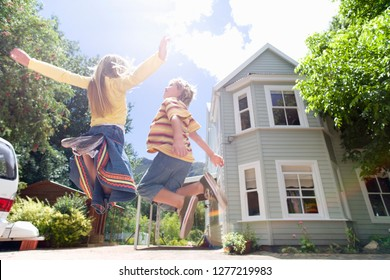 Excited children jumping in air playing on driveway outside house