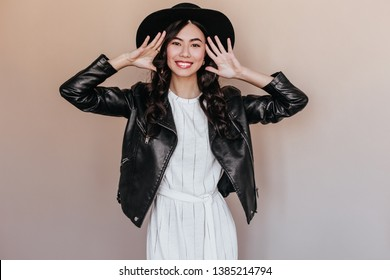 Excited chinese girl in black hat looking at camera. Front view of amazing asian model in leather jacket posing with smile.