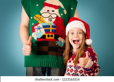 Excited Christmas Girl Giving Thumbs Up in Ugly Sweater with Dad