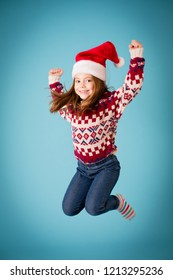 Excited Christmas Girl Jumping in Celebration, Isolated on Teal