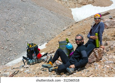 Excited Climbers. Young Man and Woman Traveling Outdoor Relaxing on Rocky Moraine with Backpacks and Thermoses Drinking Refreshments Fun Pleasure Casual Sporty Style Clothing