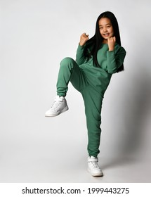 Excited contented happy smiling Asian girl ten years old in green clothes, standing in a one-legged position, clasped her arms to her chest. Reception from karate or martial arts.