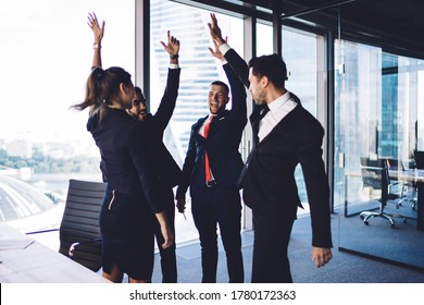 Excited corporate partners dressed in formal wear enjoying synergy association during working day for brainstorming collaboration, successful men and woman celebrating approved business project
