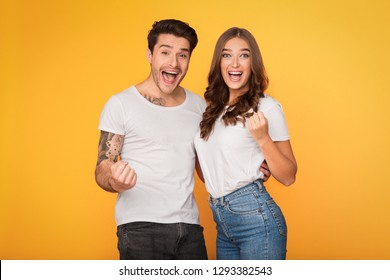Excited couple celebrating success, clenching fists like winners over yellow background