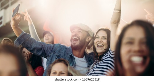 Excited couple cheering  and taking selfie while at stadium. Cheerful soccer fans taking selfie while watching match in stadium.