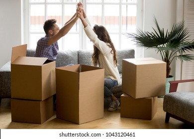 Excited couple holding hands happy to move into new home, young family celebrate moving day sitting on sofa with boxes, tenants renters or owners relocating into house start living together concept