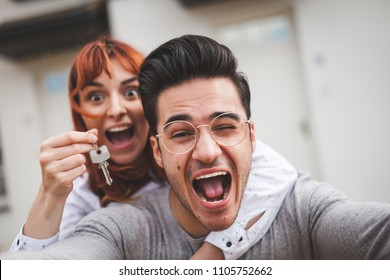 Excited couple with keys to their new home hugging and looking at camera taking selfie