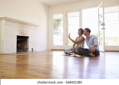 Excited Couple Planning Decoration Of New Home