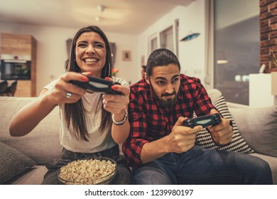 Excited couple is playing video games at home sitting on sofa. They have great weekend in nice company indoors.