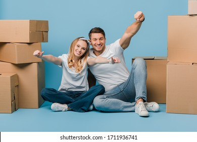 excited couple showing thumbs up while sitting with cardboard boxes for relocation on blue