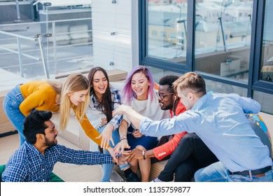 Excited creative group of multiethnic people co-workers giving high-five in outdoor meeting room at creative office