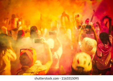 An excited crowd celebrating by throwing colored powder in the air.
